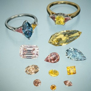 Two rings: (left) 1.86-ct. Fancy Deep blue diamond flanked by pink and yellow triangular cut diamonds, (right) 1.11-ct. Fancy intense yellow-green diamond flanked by 2 triangular cut orangy-pink diamonds. Photo courtesy of American Siba Corp, Moses Jewelers, Isaac Wold and Lazar Wolf.