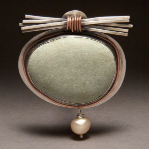 The appeal of John Walsh's Zen Bundle brooch comes from the artful selection and placement of the materials. Walsh has taken a simple object, a river stone, and set it in a silver bezel mounting, with a bundle of sticks made of silver and a simple pearl adornment, showcasing? Emphasizing? Highlighting? its natural beauty.