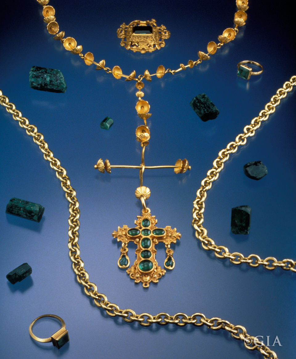 Some of the treasures of the Atocha: a gold rosary with an emerald cross, two emerald rings, an emerald brooch, a gold chain, and loose uncut Colombian emeralds. Photo by Shane F. McClure/GIA.