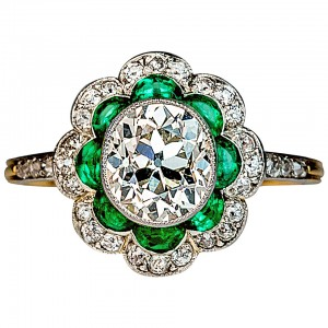 This 1920sl platinum and 18K gold ring with an approximately 1.50 ct oval diamond. Eight half-moon shaped emeralds look like petals in this floral design. Courtesy: 1stdibs.com