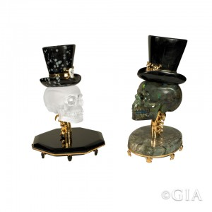Luis Alberto Quispe Aparicio's sculptures capture the spirit of the holiday. The skull of Top Hat Gentle-Skull (left) is carved from Madagascar rock crystal quartz and sits atop gold vermeil vertebrae on an obsidian base. The skull sports a snowflake obsidian hat with a gold vermeil hat band adorned with a rock crystal skull. Cavalier's skull (right) is carved from Madagascar labradorite and sits on a labradorite base. Its hat is obsidian, and gold vermeil is used for the hat band as well as the vertebrae. Photo: Orasa Weldon/GIA. Courtesy: Luis Alberto Quispe Aparicio