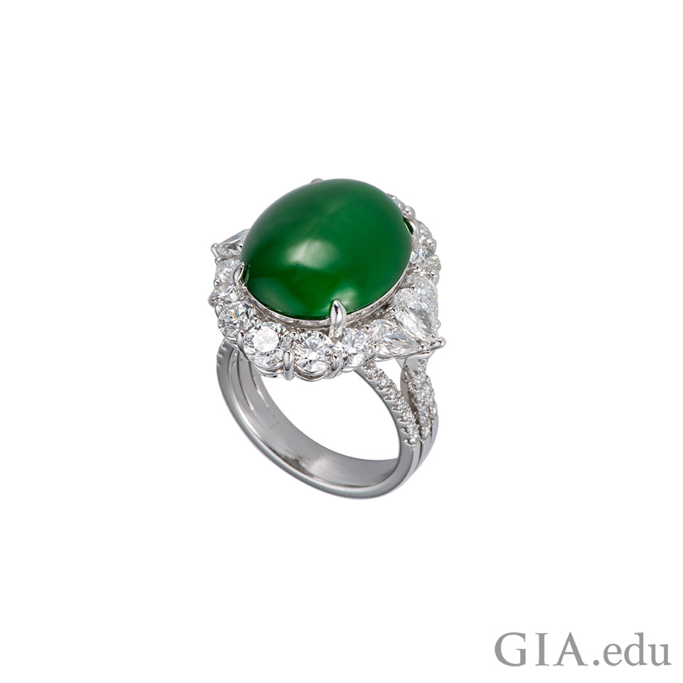 Green jadeite cabochon ring surrounded with colorless diamonds.