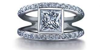 Split shank ring set with square-shaped center diamond and smaller diamonds along the shank.