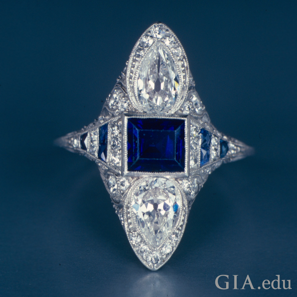 An emerald-cut sapphire sitting between two pear-shaped diamonds