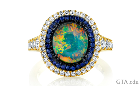 Black opal, sapphire and diamond ring set in 18k yellow gold with black rhodium