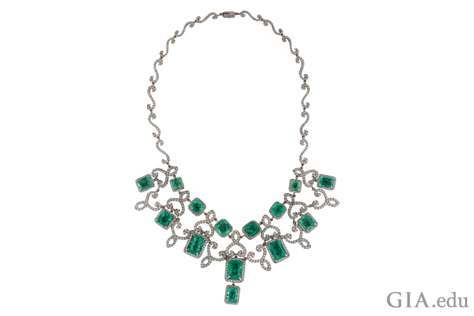 14K white gold bib necklace featuring 12.93 carats of pavé set round brilliant diamonds and 45.43 carats of prong-set emeralds
