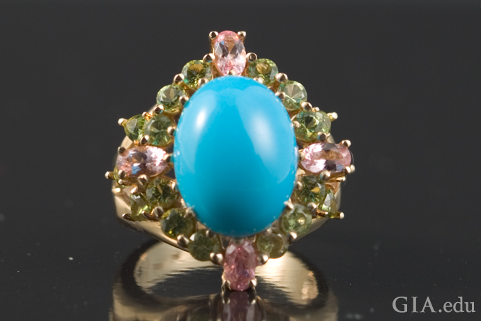 An oval cabochon cut turquoise cabochon ring surrounded by peridot and pink tourmaline.