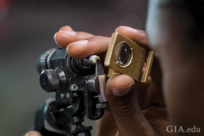 A diamond cutter at Diacore Botswana examines the initial facets made on a fancy yellow diamond.