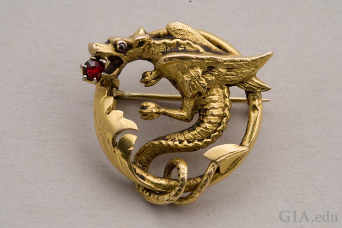 18K gold Art Nouveau era pin depicts a dragon or gryphon with a red garnet in its mouth.
