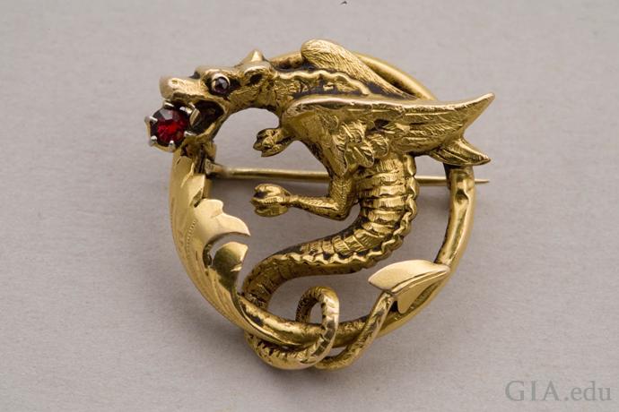 口に赤いガーネットを持つ、龍に似たギリシャ神話の怪物グリフォンを描く、18Kゴールドのアールヌーボー時代のピン。