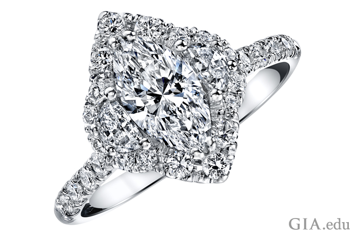 Three stone marquise cut diamond engagement ring with half-moon cut diamonds and a halo of round brilliant cuts.