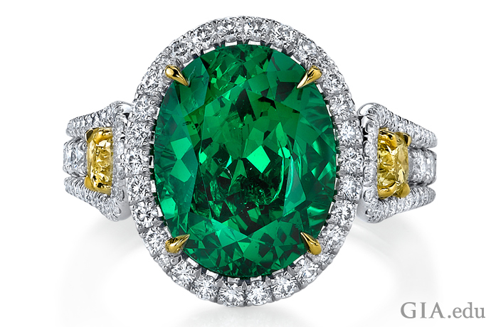 A 5.55 ct oval tsavorite garnet ring, with two fancy yellow diamonds weighing a total of 0.71 ct, and 136 round diamonds weighing 1.02 ct total weight, set in platinum.