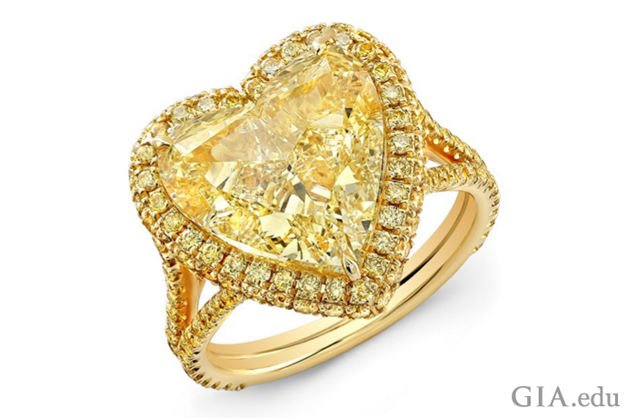 Fancy yellow 7.02 carat (ct) symmetrical heart-shaped diamond surrounded by 1.08 carats of yellow pavé-set diamonds.