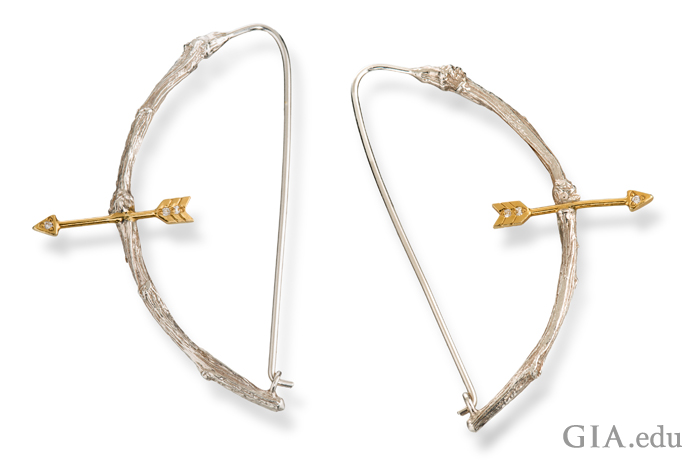 18K gold, sterling silver and diamond-accented earrings. The bow is carved to resemble pieces of knotted wood.