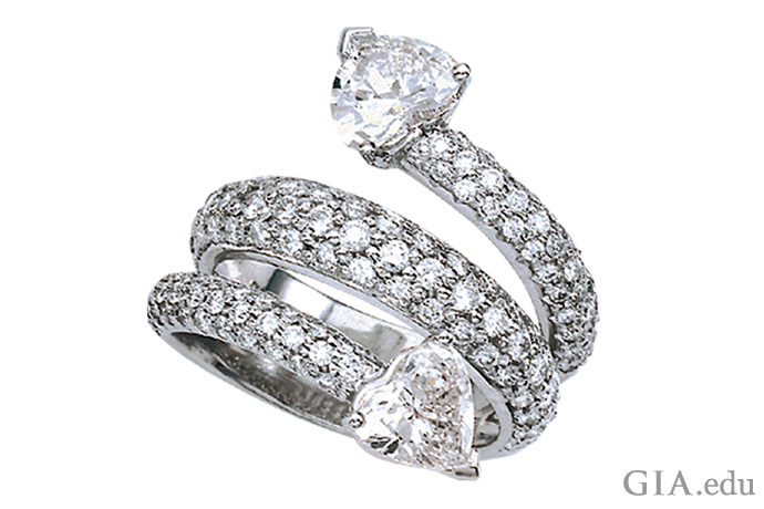 A Platinum ring with two heart-shaped diamonds joined by a coil of pavé-set diamonds.