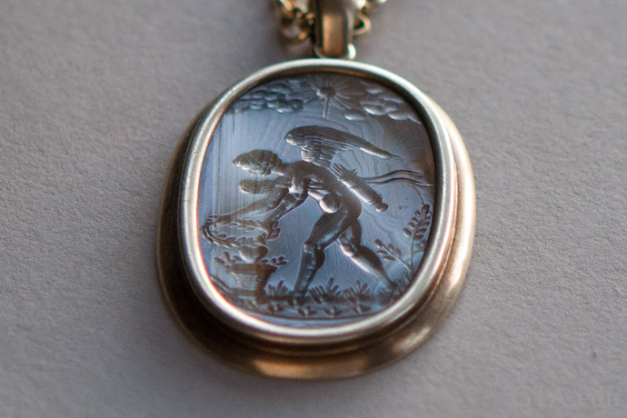 An antique agate intaglio pendant (circa 1600) depicts Eros as a muscular, winged youth.