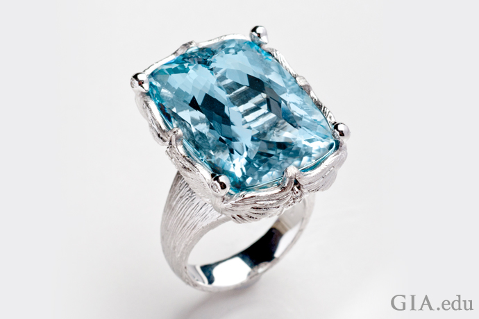 "Disguised as ""love doves,"" 14K white gold prongs hold a 32 ct cushion cut aquamarine from Brazil."