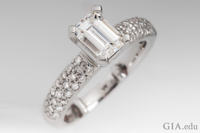 Diamond engagement ring featuring pavé set diamonds and a 1.00 carat emerald cut center stone.