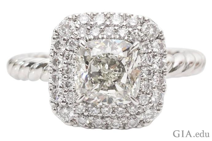 クッションカットのセンターストーン(1.17カラット)を囲む、二重ヘイローセッティングのダイヤモンドの婚約指輪。