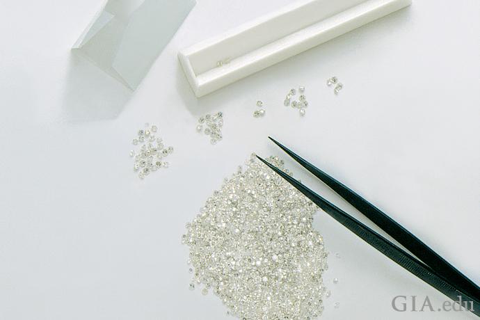 Hundreds of melee diamonds glitter on a table.
