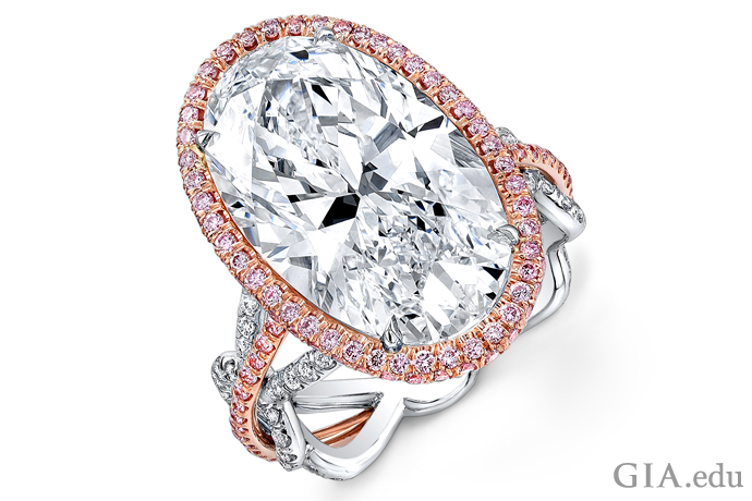 A 10.92 ct oval diamond engagement ring, accented with a halo of Fancy pink melee diamonds