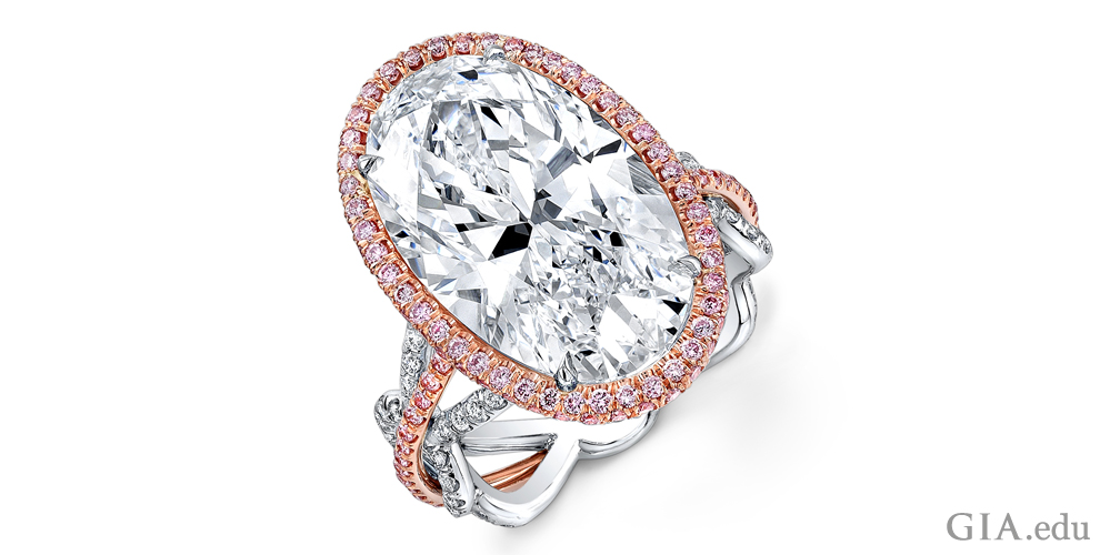 A 10.92 carat (ct) oval diamond engagement ring accented with fancy pink and white melee set in 18K rose gold and platinum