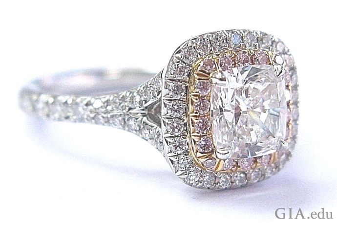 Cushion cut diamond and platinum engagement ring surrounded by a halo of melee and natural pink diamonds