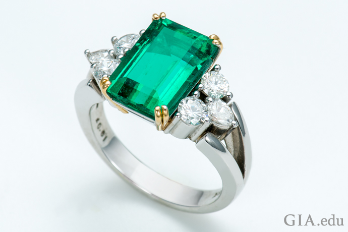 A 3.69 ct emerald ring with six diamond side stones