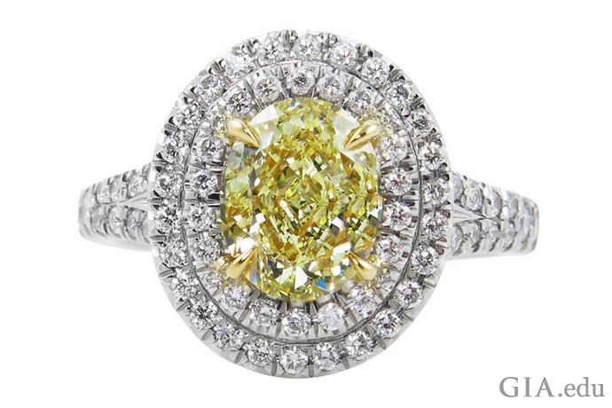 2つのメレーダイヤモンドのヘイローに囲まれた1.58ctのファンシーイエローのオーバルシェイプ・ダイヤモンド