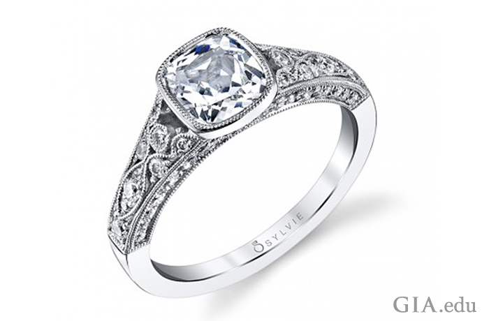 An engagement ring featuring a bezel-set 1.00 ct cushion cut diamond, accented by 0.54 carats of diamonds in the shank