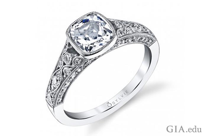 ベゼルセットの1.00ctのクッションカットダイヤモンドが特徴の婚約指輪、シャンクは0.54カラットのダイヤモンドのアクセント付き