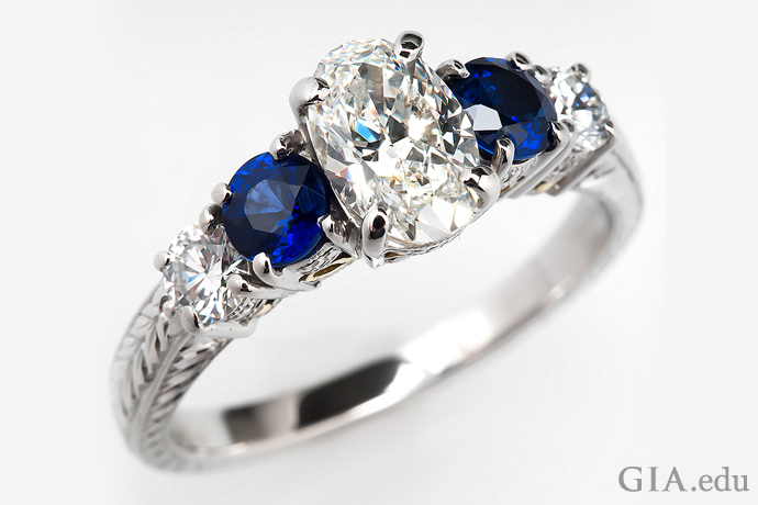 A 0.90 ct oval diamond engagement ring, flanked by two round sapphires and round diamond side stones