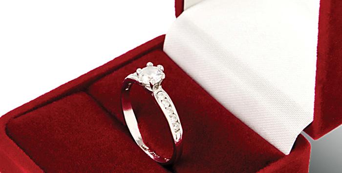 镶嵌着圆形明亮式主石的夹镶订婚钻石戒指,放置在红色订婚戒指盒中。