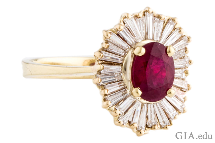 "An 18K yellow gold prong-set cocktail ring with a ruby center stone, accented with tapered baguettes to make a ""ballerina setting."""