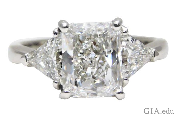 3 克拉雷地恩切磨式样的钻石两侧镶嵌着两颗 0.70 克拉的 Trilliant。