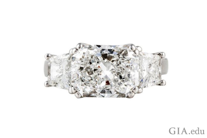 精美的戒指上镶嵌着一颗 4.15 克拉的钻石和 1.25 克拉梯形切工副石。