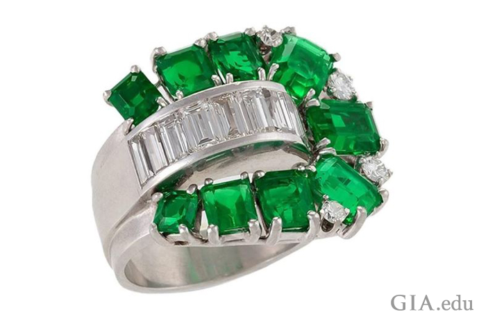 A poetic interpretation of this Retro-era engagement ring – a footbridge of channel-set baguettes is surrounded by tracks of emeralds.