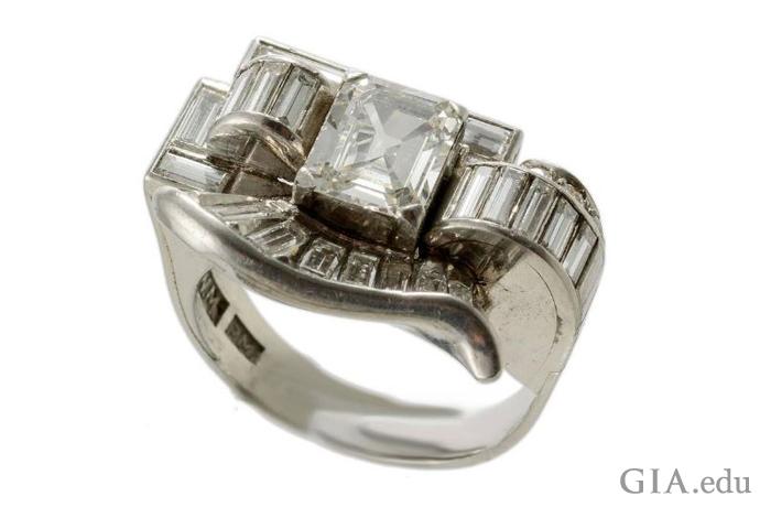 在这枚复古时代的古董订婚戒指中,狭长的方形钻石整齐排列,形成一道曲线。 主石是一颗1.50克拉的祖母绿切工钻石。