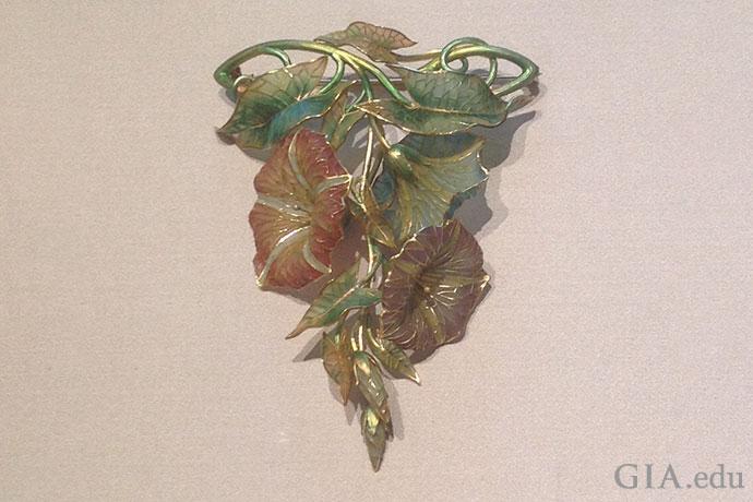 このゴールドのプリカジュール技法でエナメルを施したコサージュの装飾は、1900年頃のもので、ピンク、青、薄紫の朝顔が描かれている。