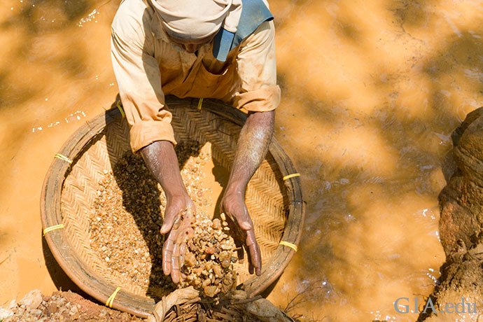 Using the same rudimentary washing techniques as generations before them in Sri Lanka, miners search for sapphire among the gravels in a local stream.