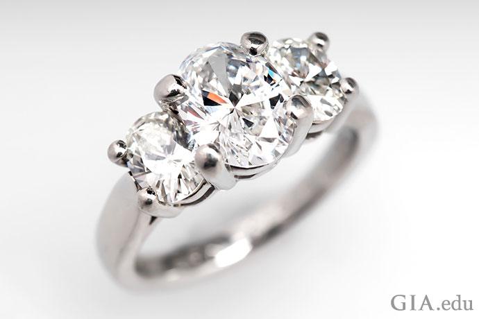 这枚闪闪发亮的三石铂金订婚戒指镶嵌着一颗1.57克拉的椭圆形钻石主石,充满浪漫气质。