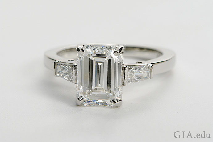 This 2.71 ct diamond showcases the stately beauty of an emerald cut, The center diamond is accentuated by two tapered baguettes.