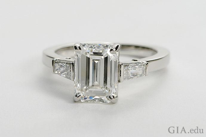 这颗2.71克拉的钻石展现出祖母绿切工的庄重之美,两颗梯钻突显出主石的光芒。