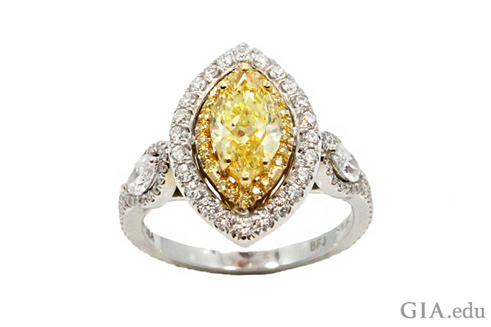 This sunny stunner of an engagement ring boasts a 1.10 ct marquise yellow diamond and two white marquise diamonds in the shank, with a halo of melee diamonds surrounding the center stone.