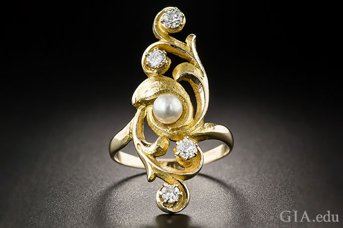 The pearl in this vintage Art Nouveau cocktail ring is like the calm eye of a storm, with a hurricane of curved lines swirling around it.