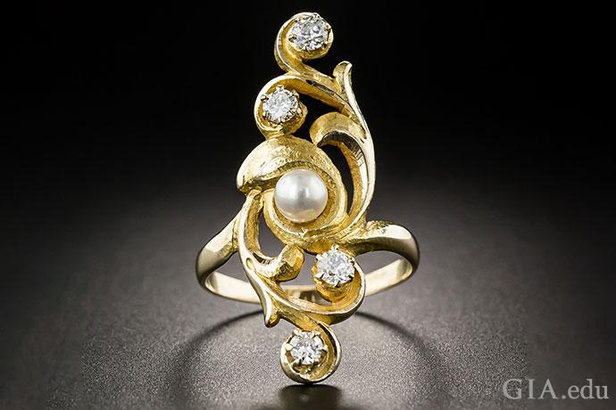 このヴィンテージアールヌーボーのカクテルリングに使われている真珠は、カーブしたラインのハリケーンがその周囲を渦巻いていて、嵐の中の穏やかな目のようである。