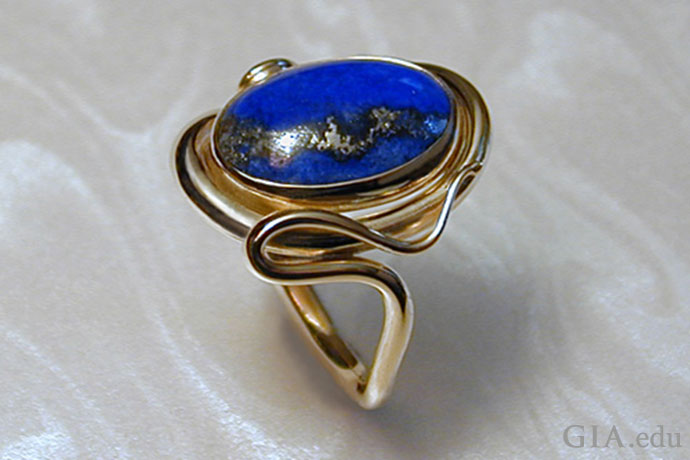 Art Nouveau lives in this contemporary ring. Lapis lazuli is the center stone, while sinuous whiplash lines slither around it.