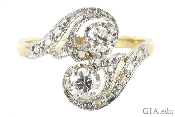 Like comets with long tails, the two main diamonds (a total of 0.36 carats) in this Art Nouveau style ring are trailed by curving diamond-studded lines that swirl throughout the ring.