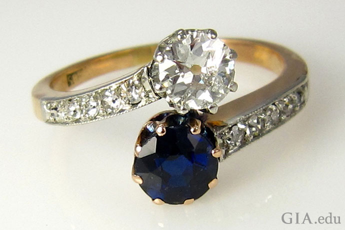 This Victorian-era (circa 1885) crossover ring, set with a sapphire and an old European cut diamond, celebrates two lives joined together in marriage.