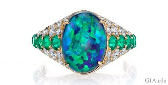 3.50 ct black opal, emerald and diamond ring. Set in 18k yellow gold.